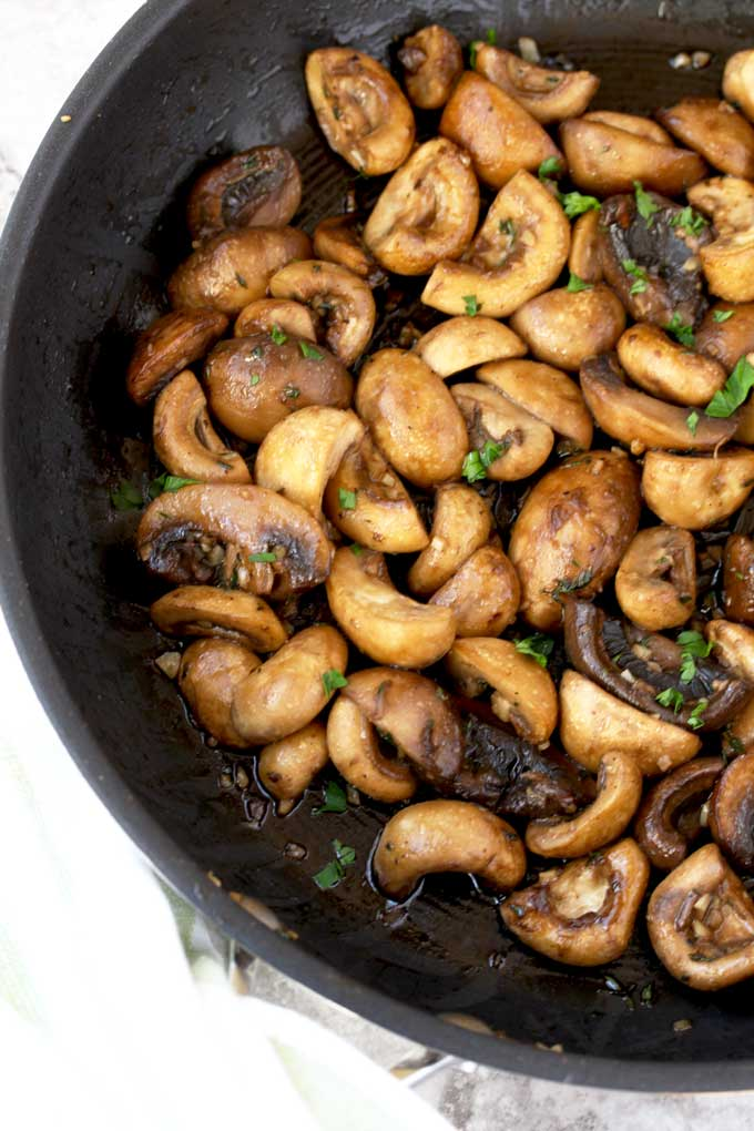 Caramelized sauteed Mushrooms in a skillet garnished with chopped parsley.