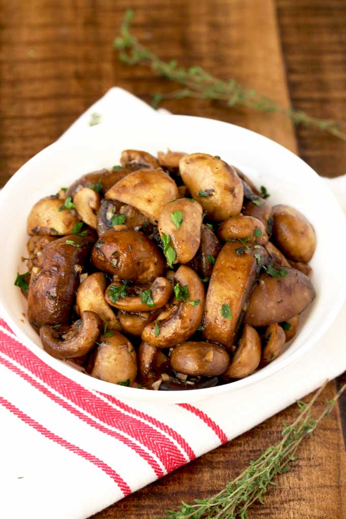 A batch of sauteed mushrooms recipe served on a white bowl.