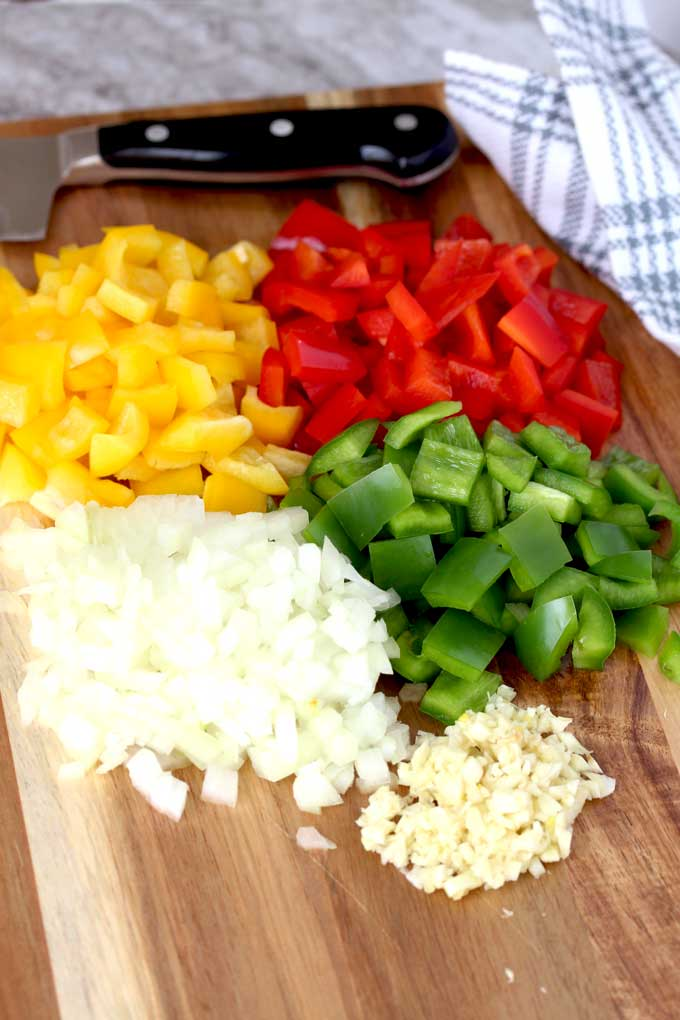 Chopped bell pepper, onions and garlic on a cutting board.