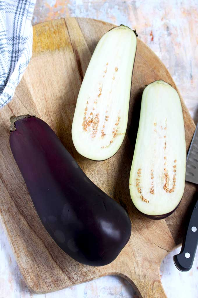 One whole eggplant and an eggplant cut in half on a cutting board.