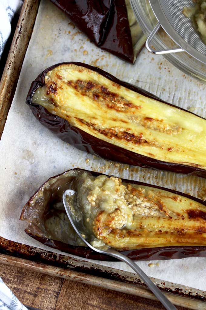 Removing the skin of a roasted eggplant.