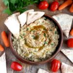 Baba Ganoush in a wooden serving bowl served with pita bread, baby carrots and tomatoes.