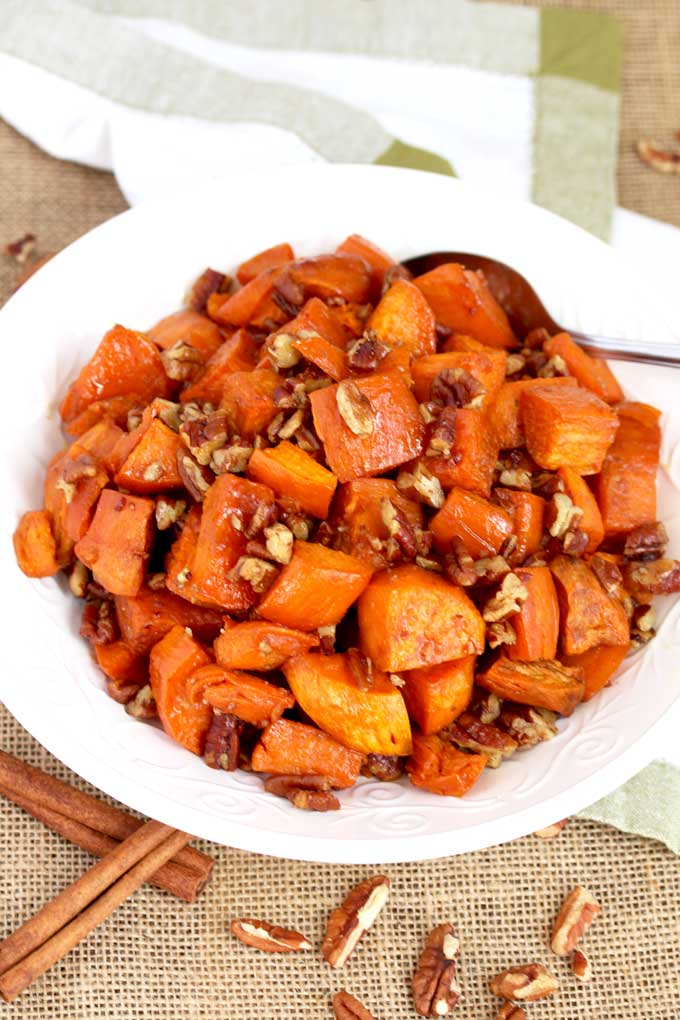 Top view of a white bowl with candied sweet potatoes and pecans.