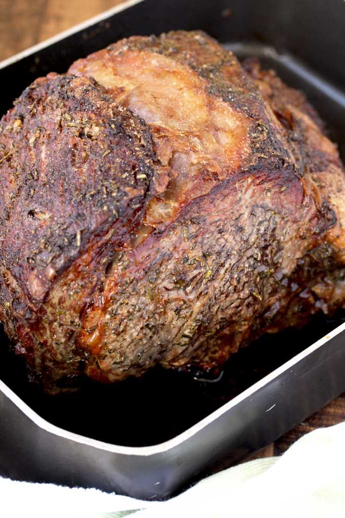 Roasted and golden brown Prime Rib Roast in a roasting pan.