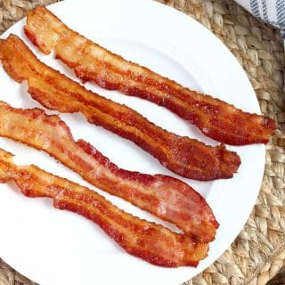 Crispy bacon slices on a white plate.