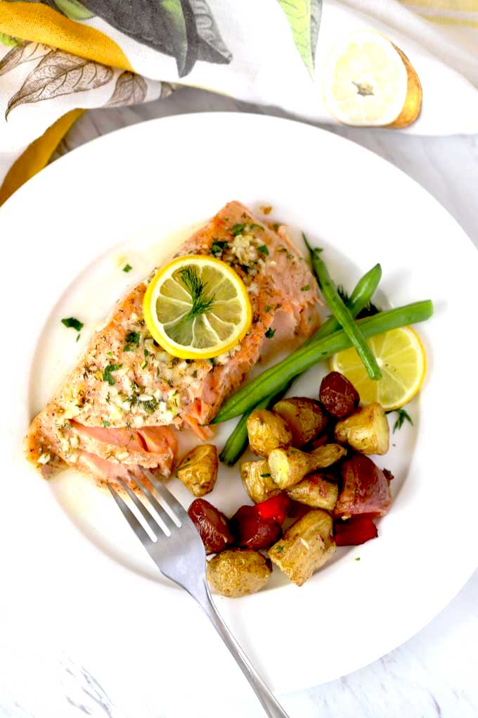 Top view of baked salmon on a white plate.