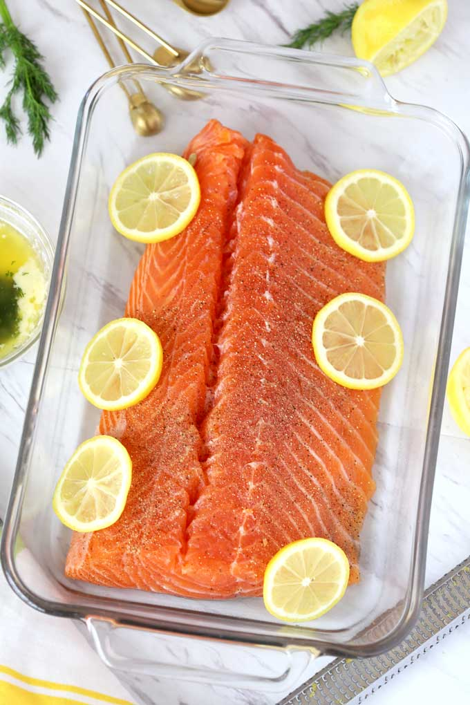 Raw salmon on a baking dish topped with lemon slices.