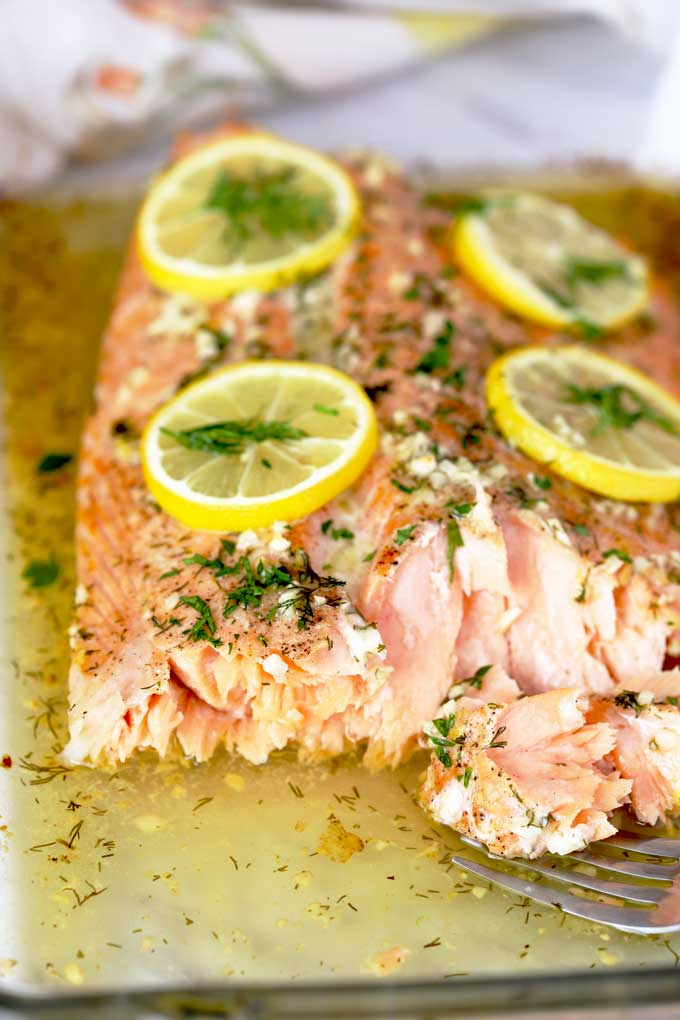Baked Salmon on a baking dish with lemon and herb.