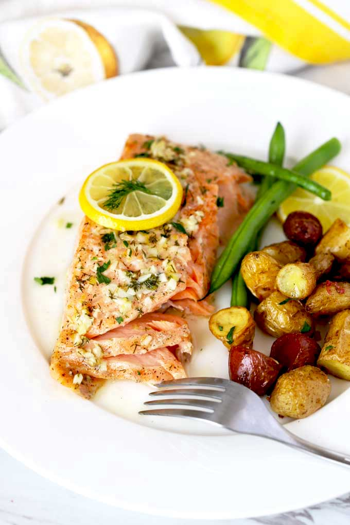 Baked salmon fillet served with roasted potatoes and green beans on a white plate.