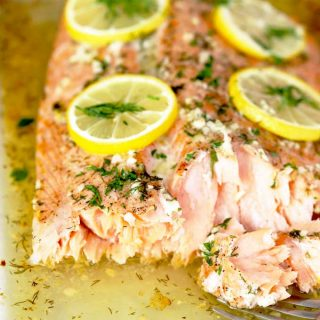 Baked Salmon Fillet topped with lemon slices on a baking dish.