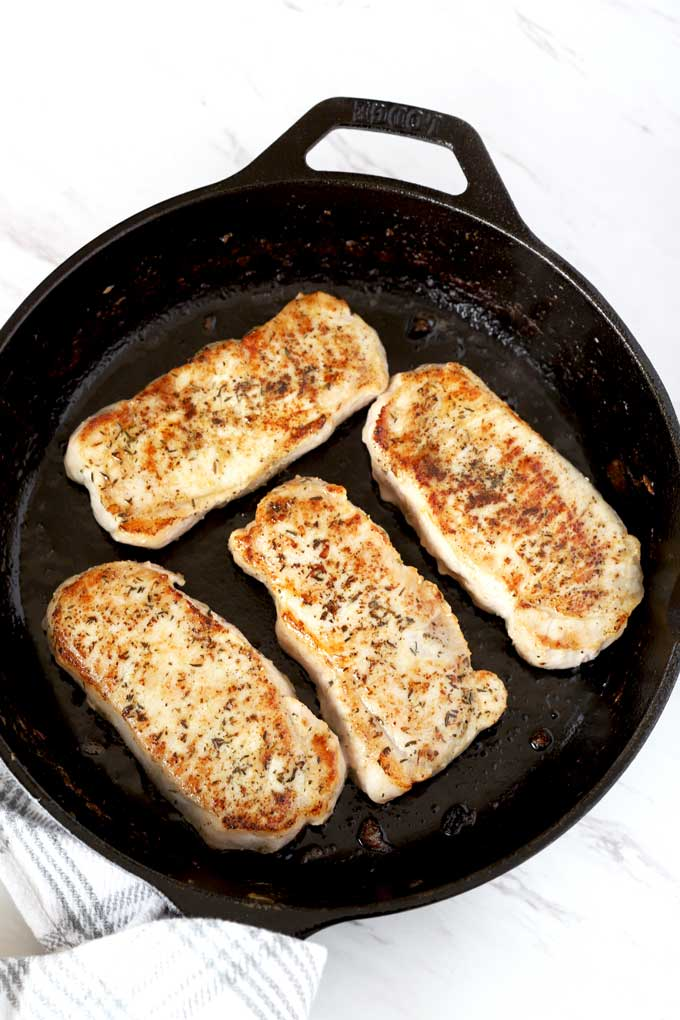 Golden pan seared pork chops in a skillet.