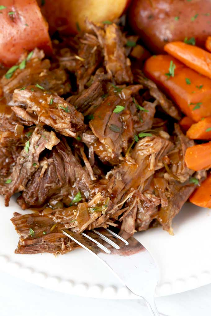 Shredded Pot Roast with Gravy on a white plate.