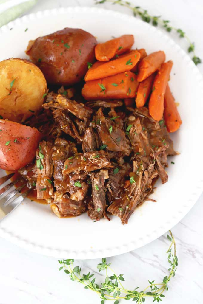 Top view of shredded instant pot pot roast served with carrots and potatoes on a white platter.