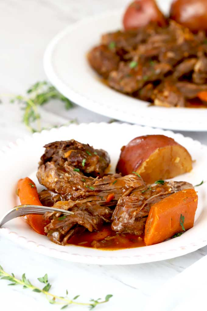 Shredded Pot Roast with carrots and potatoes on a white plate.