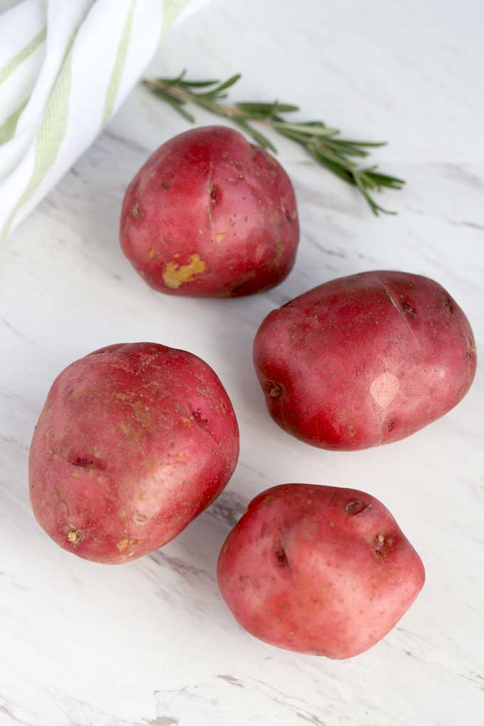 Red potatoes and fresh rosemary on a white surface.