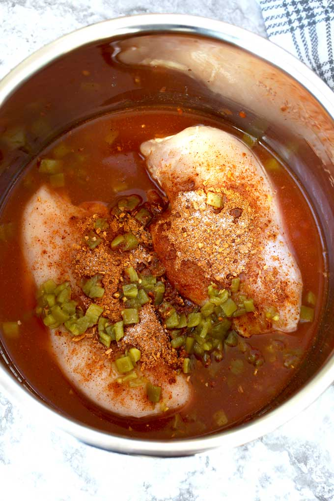 Chicken breast topped with the ingredients to make this dish inside a pressure cooker.