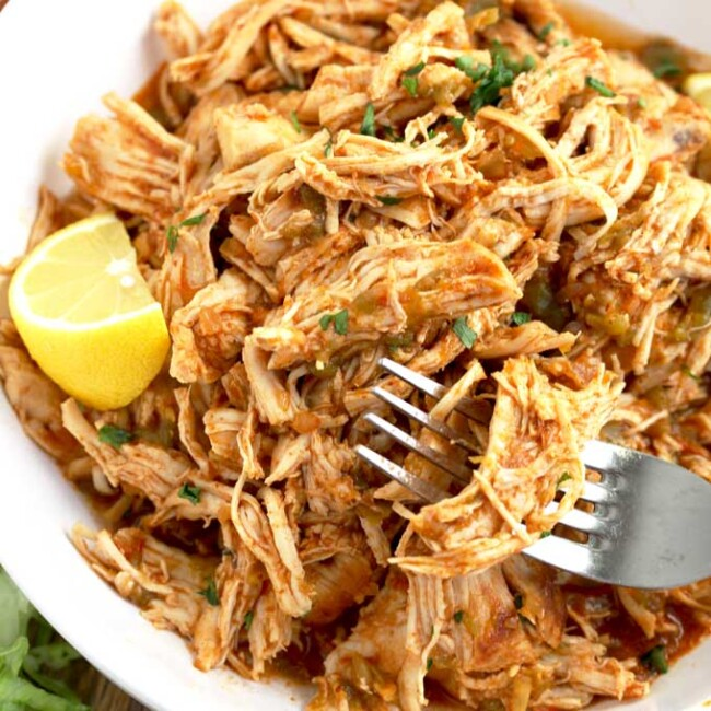 A white plate filled with instant pot shredded chicken.