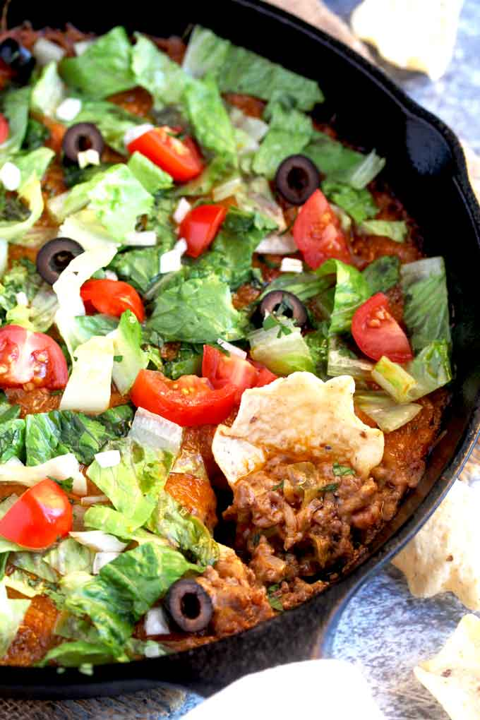 Close up of a chip scooping taco dip