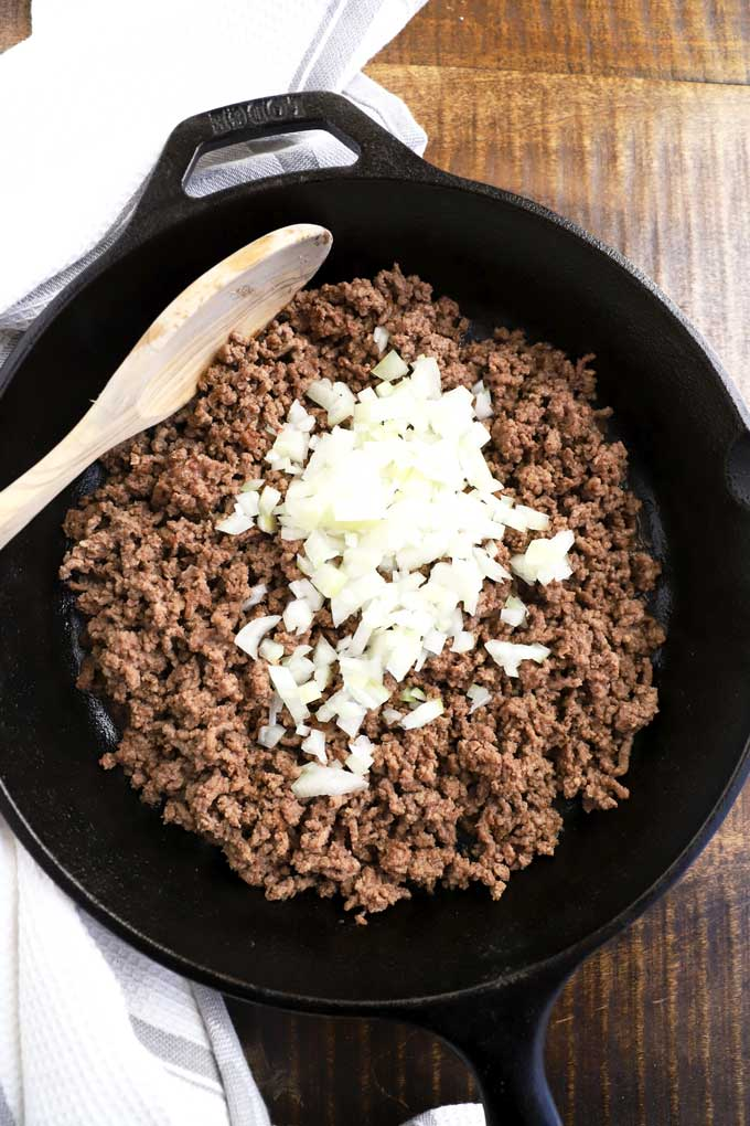 Browned ground beef and onions in a skillet.