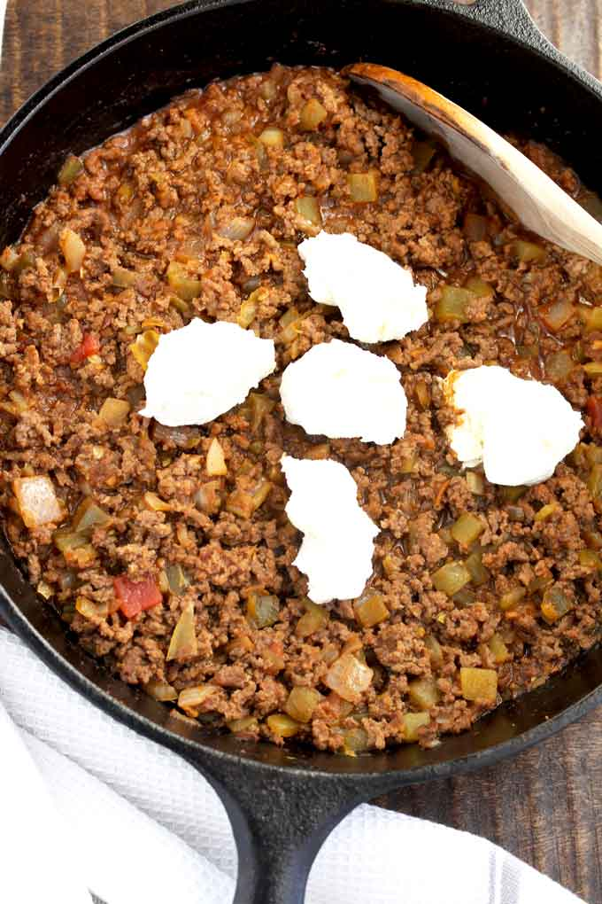 Seasoned ground beef topped with diced cream cheese in a skillet.