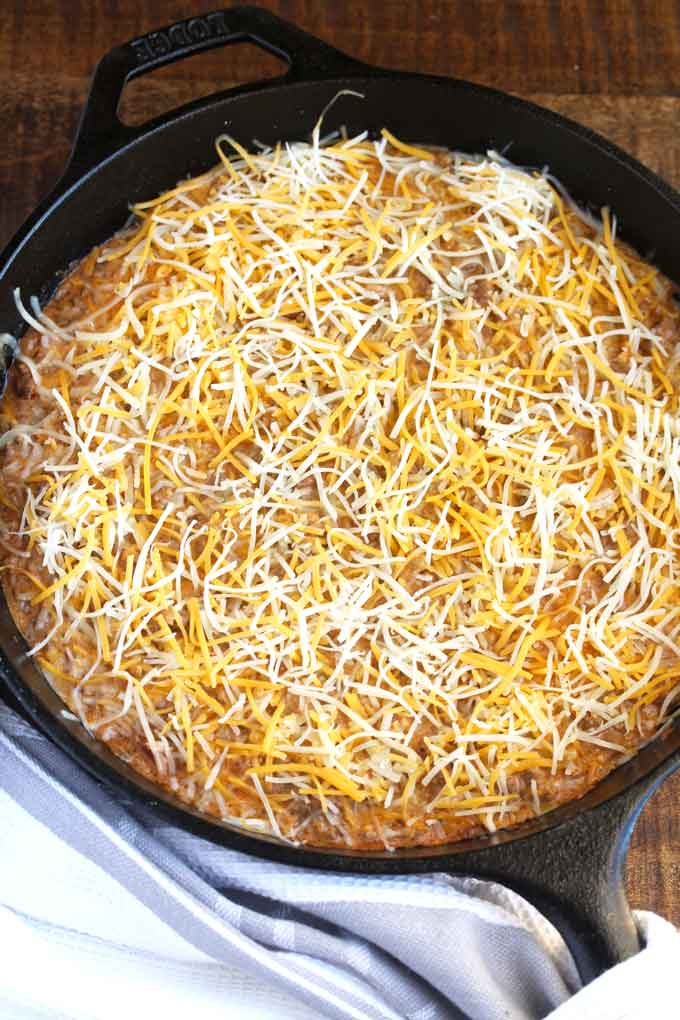 Taco Dip topped with shredded cheese in a skillet