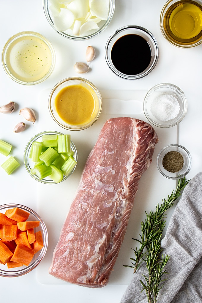 Ingredients to make Pork Loin with Honey Mustard and Herb on a white surface.