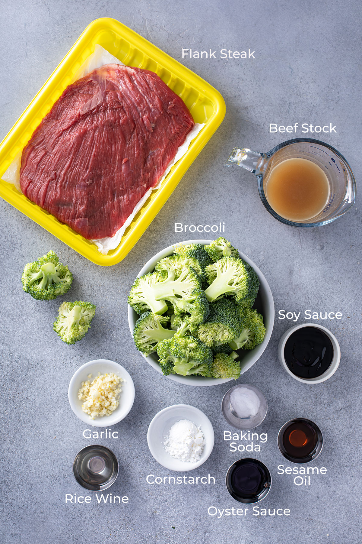 Sliced beef, broccoli and scallions on a wooden board,