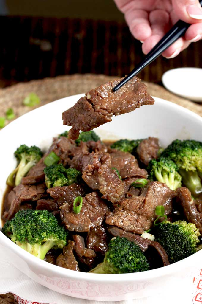 Chopsticks lifting a piece of beef from a beef with broccoli bowl.