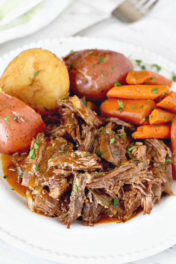 Instant Pot Pot Roast served with potatoes and carrots on a white plate.