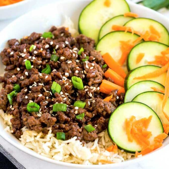 Korean ground beed over rice with cucumbers and carrots served in a white bowl.