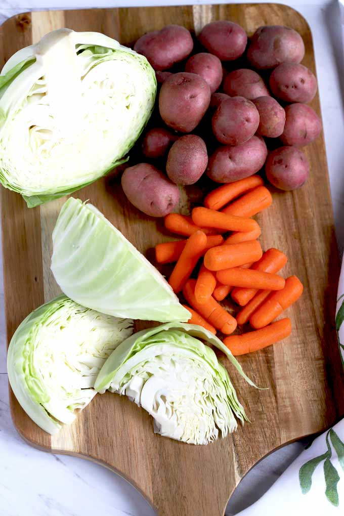 Cabbage wedges, small potatoes and baby carrots on a wooden board.