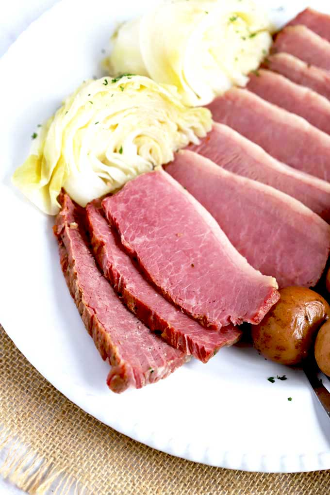 Pressure Cooker Corned Beef sliced and served with cabbage and potatoes on a white plate.