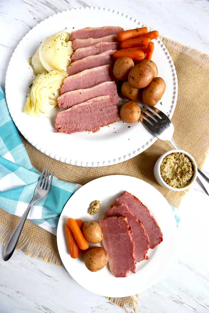 A platter filled with Corned Beef, Cabbage, Potatoes and Carrots and a small plate served with corned beef, potatoes and carrots.