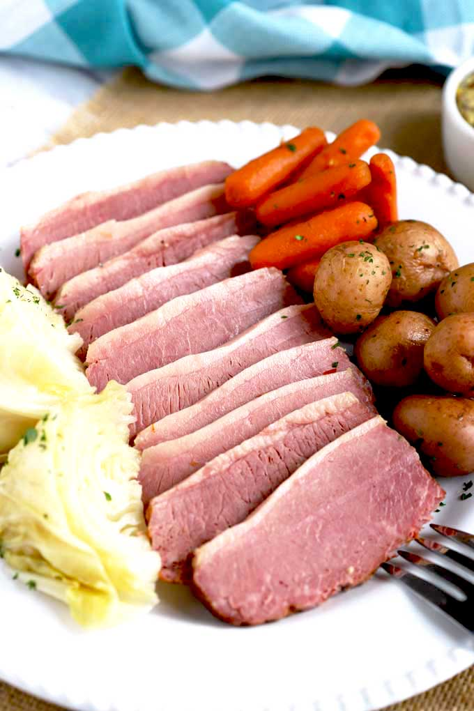 Pressure Cooker Corned Beef Sliced and served with cabbage, potatoes and carrots on a white platter.