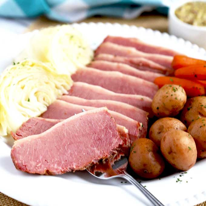 Sliced Pressure Cooker Corned Beef on a platter with cabbage wedges and potatoes.