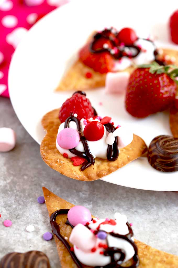 Heart shape baked cinnamon sugar wonton topped with whipped cream, raspberry, candy and chocolate sauce.