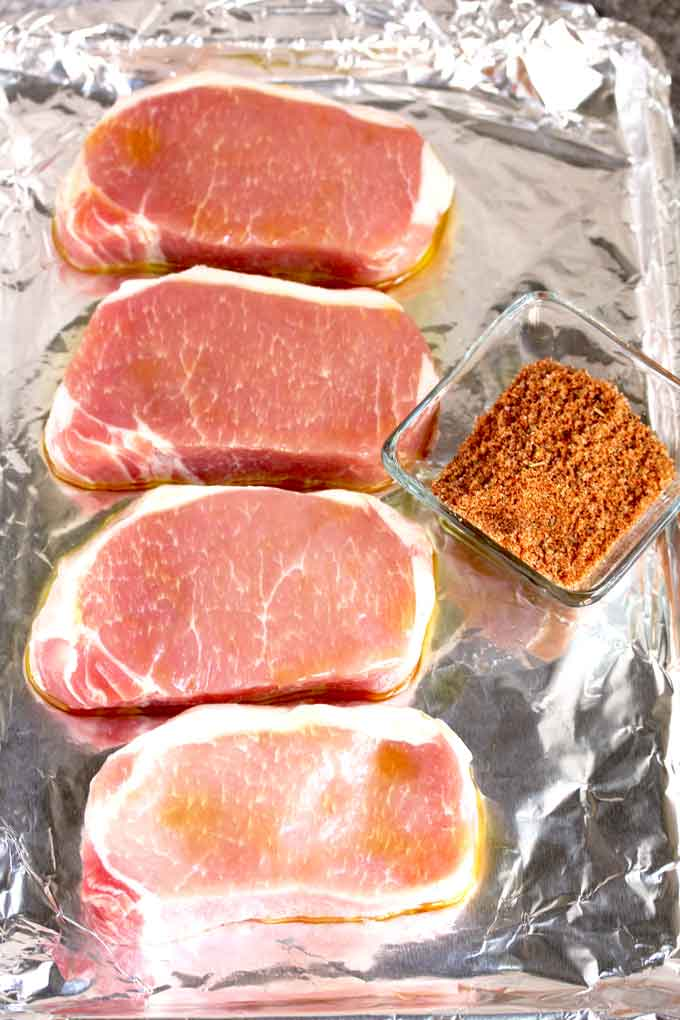 Raw pork chops on a sheet pan and a bowl of dry rub mix.