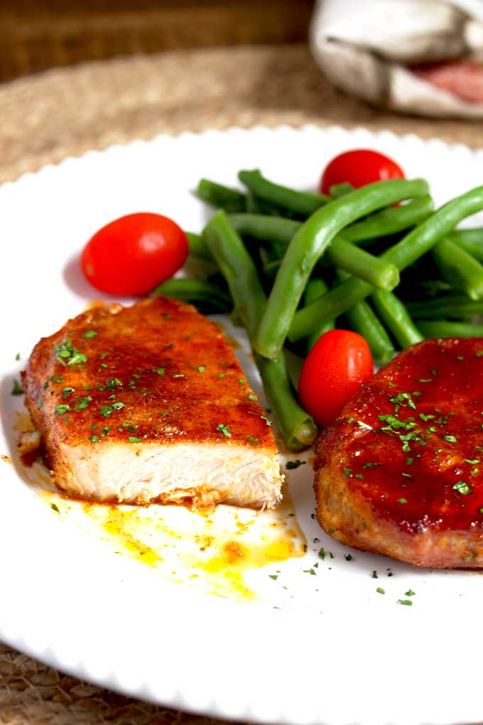 Baked Pork chop cut up served with green beans and tomatoes.