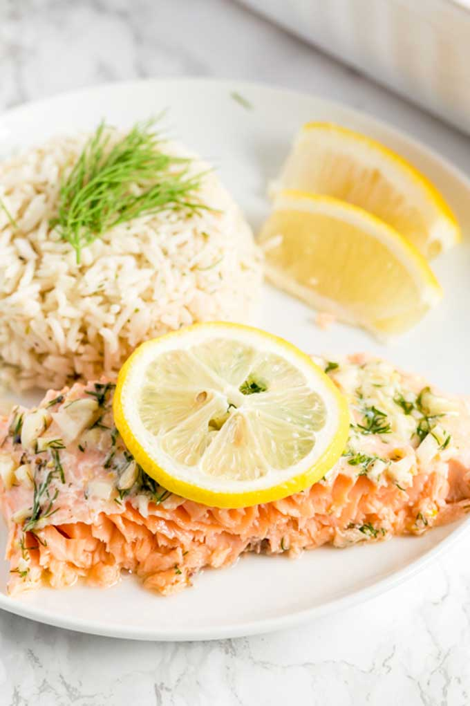 A piece of salmon served with rice and garnished with sliced lemons.
