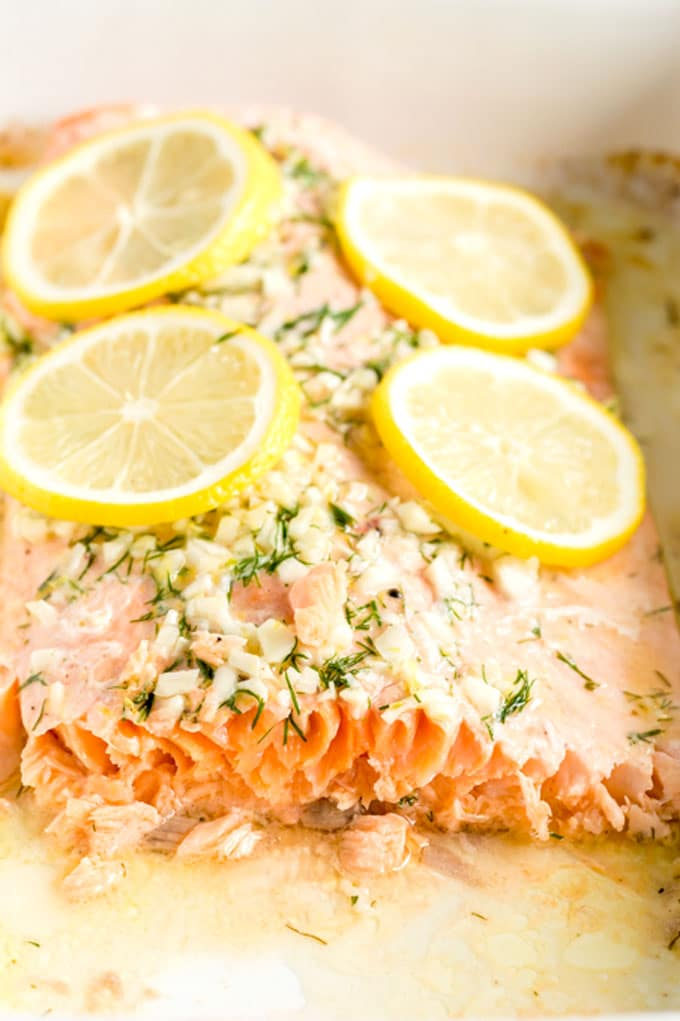 A piece of salmon filet baked and topped with lemon inside a baking dish.