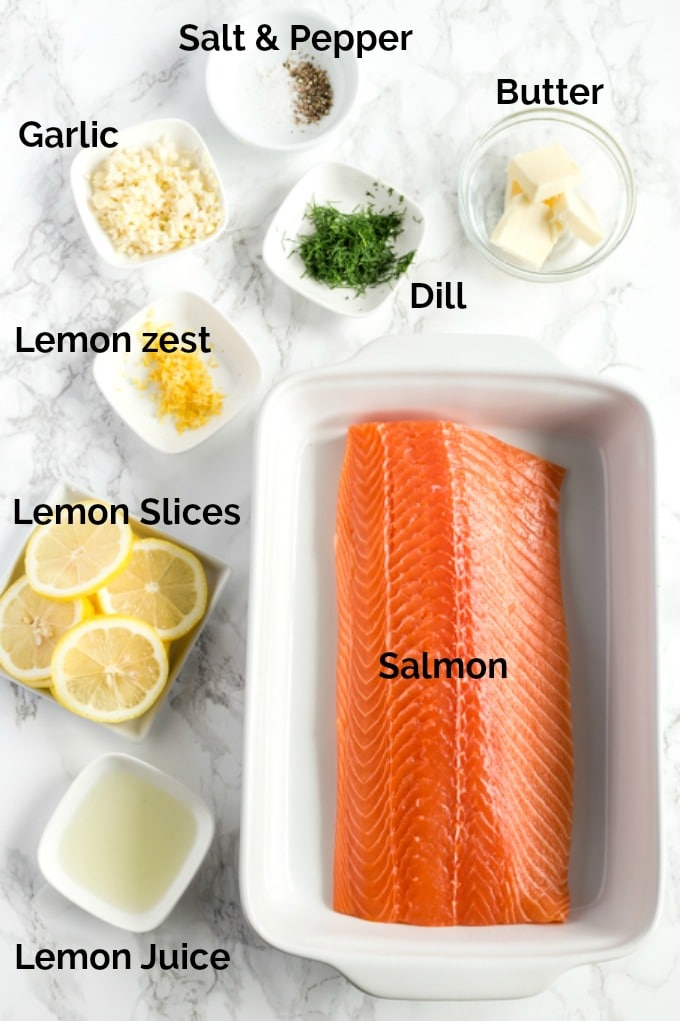 Ingredients to make baked salmon on a white surface.