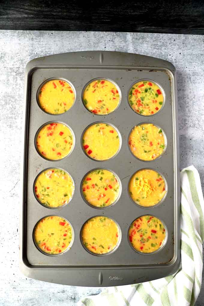 Muffin tin filled with egg mixture, veggies and cheese.