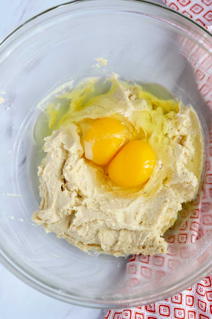 Creamed butter and sugars in a bowl topped with eggs.