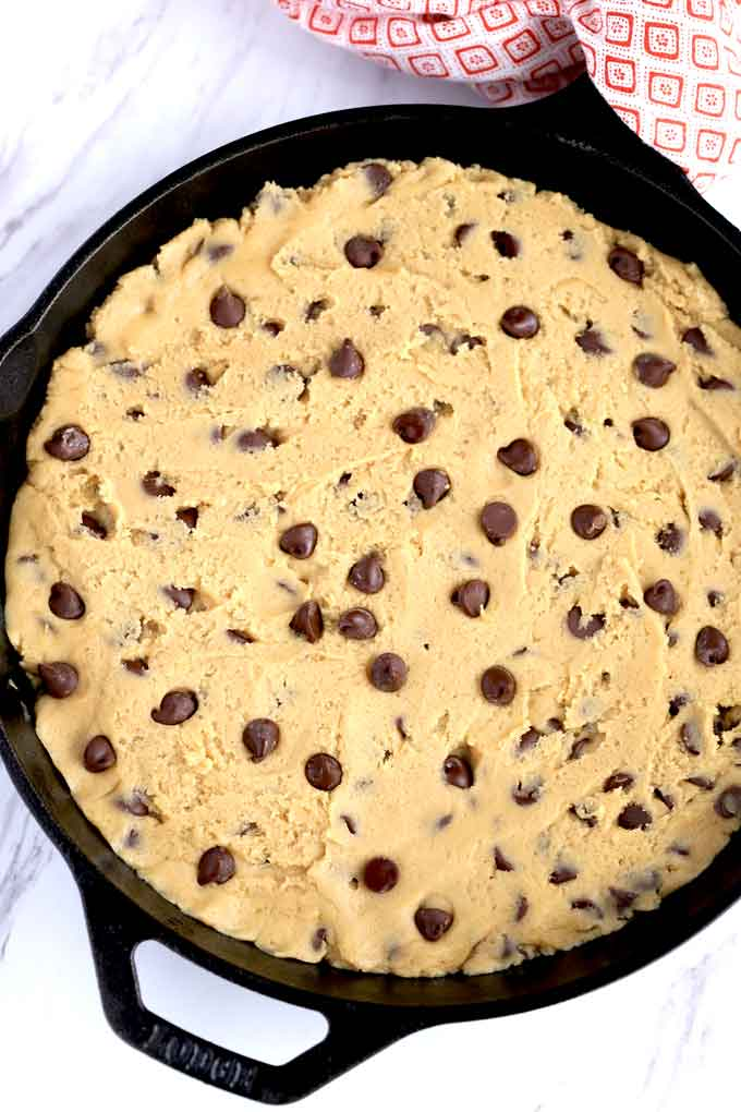 Chocolate chip cookie dough pressed into a skillet.