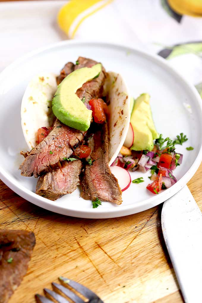 Sliced carne asada stuffed in a flour tortilla with pico de gallo and avocado slices.