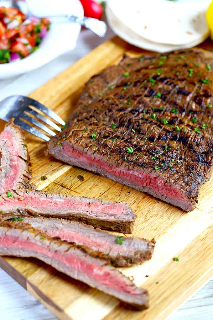 Grilled flank steak carne asada sliced on a cutting board.