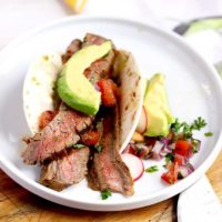 Grilled and sliced Carne Asada stuffed in a tortilla and topped with avocado