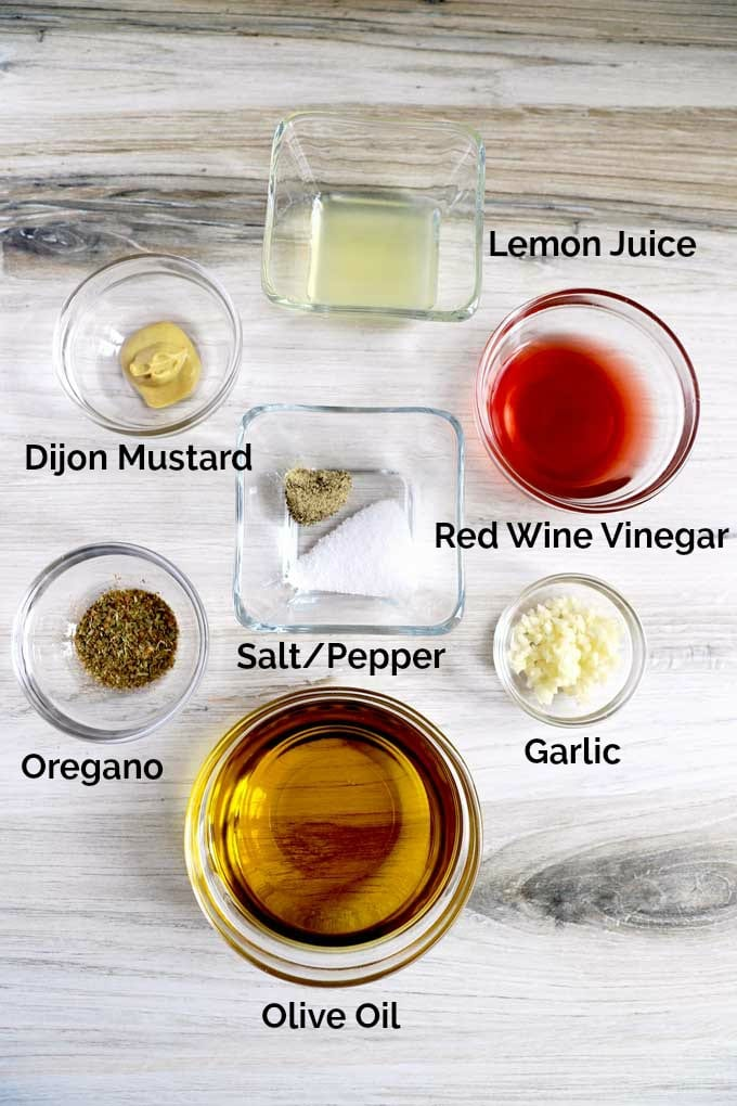 Ingredients to make Greek vinaigrette in small bowls over a white wooden counter.