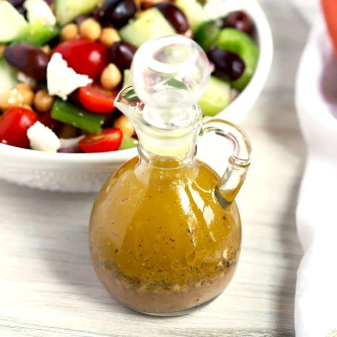 Greek Vinaigrette next to a bowl filled with Greek Salad
