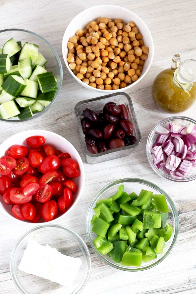 Bowls filled with the ingredients to make this easy Mediterranean salad